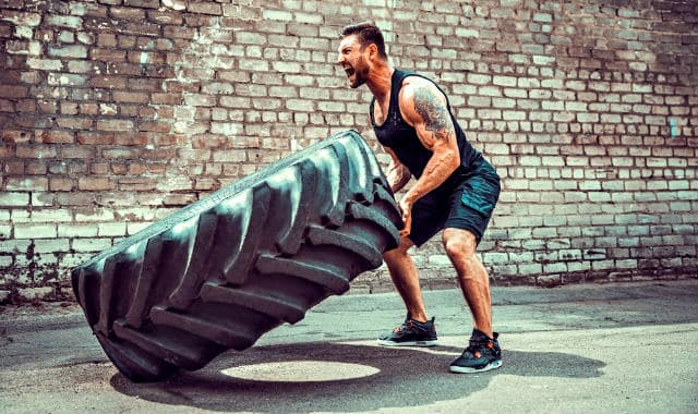 bearded man training with a car tire
