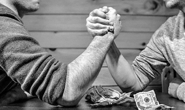 two man competing in an arm wrestling with money as wager