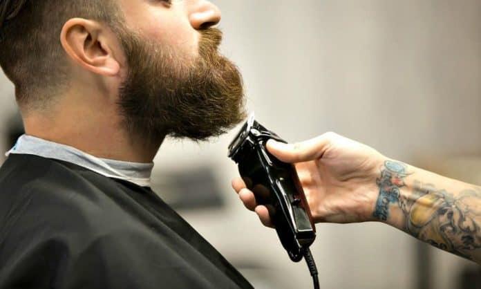 barber using beard trimmer on mans facial hair