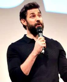John Krasinski giving a speech with a microphone and a full beard