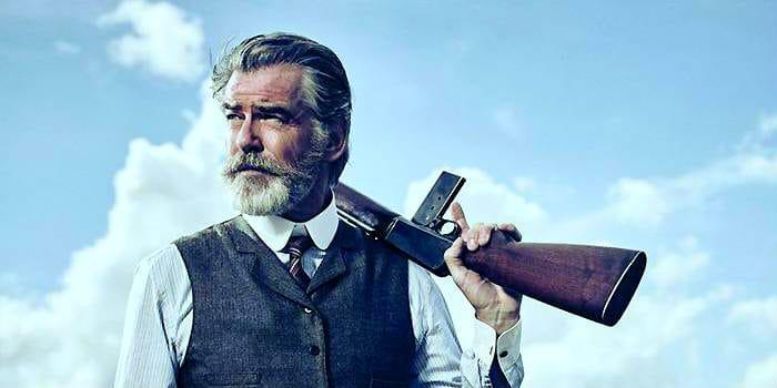 Pierce Brosnan looking intimidating with a gun and grey beard