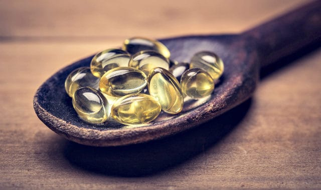 vitamin d capsules in a spoon