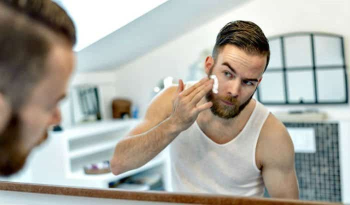 man using a beard growth cream on his face