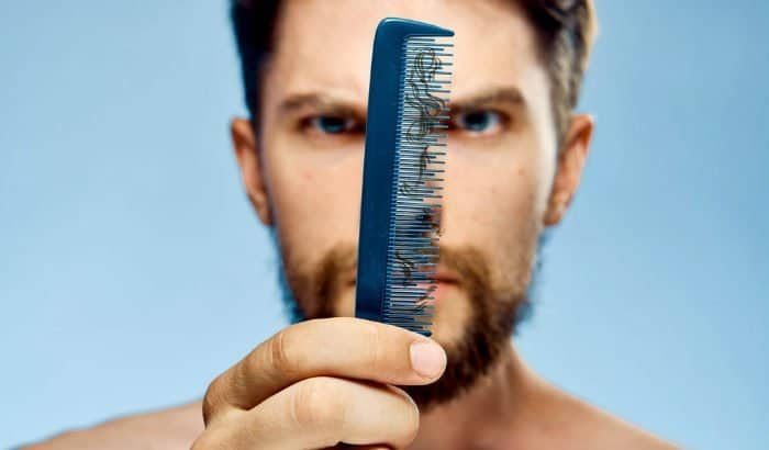man looking at damaged beard hairs