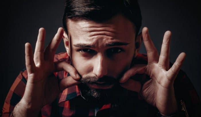 man putting vaseline on beard