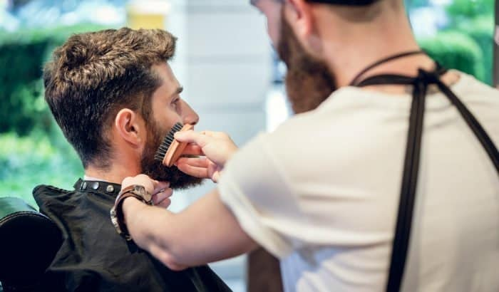 barber using a small beard brush