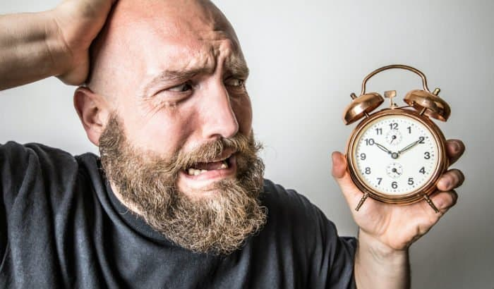 bearded man looking at a clock