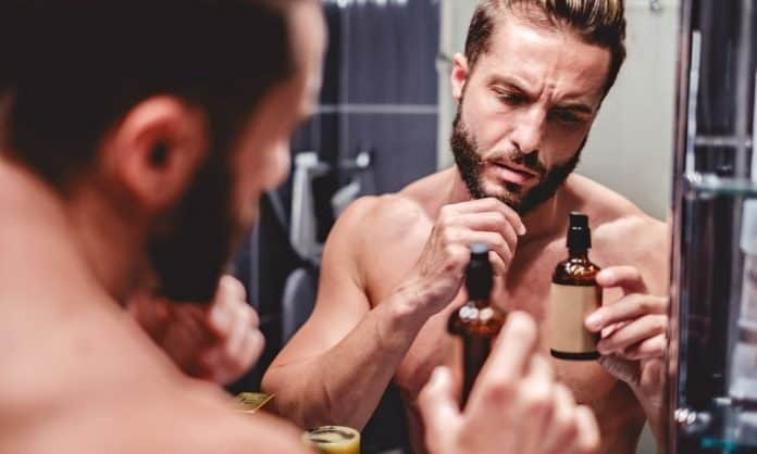 man looking at beard oil ingredient label