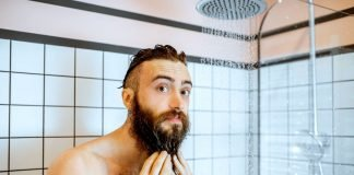 man cleaning beard in the shower