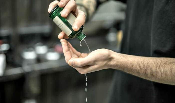 man pouring beard oil