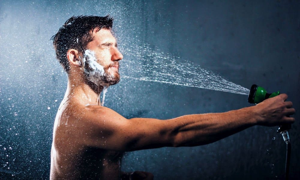 man washing his beard with a garden hose