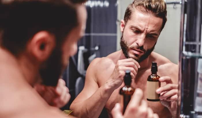 man looking at beard oil bottle