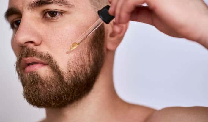 man using argan oil on his beard cheek