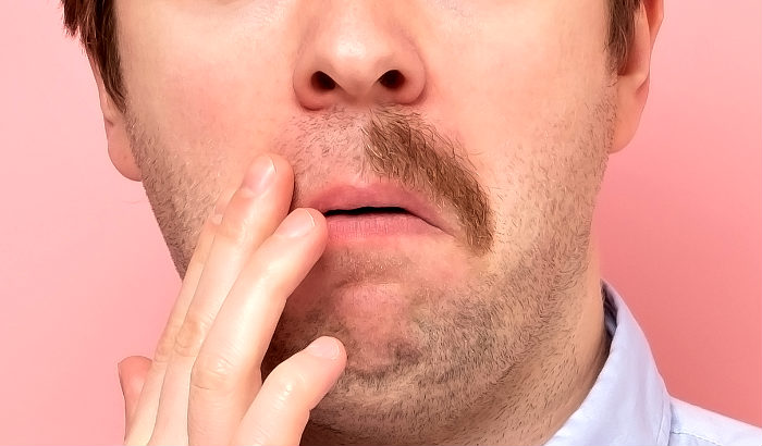 man with mustache half shaved off