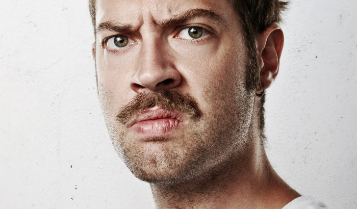 serious looking man with thick mustache