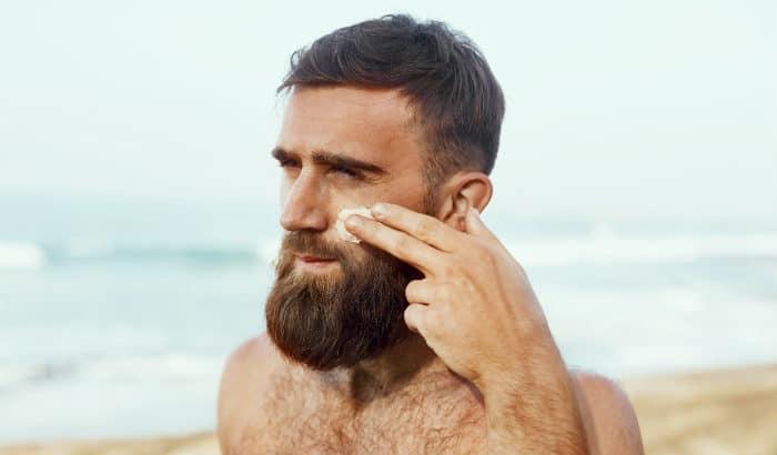 man applying aloe vera lotion to face