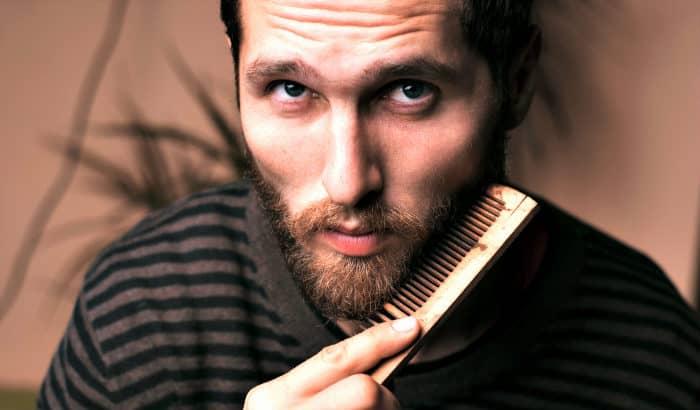 man using a big wooden beard comb