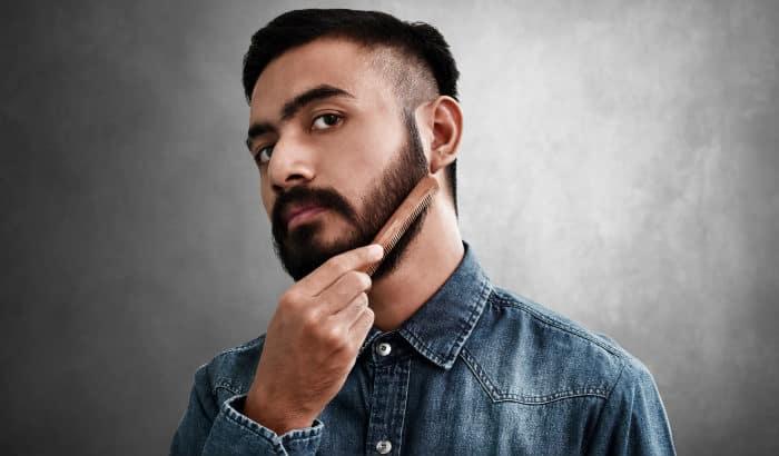 man with dark beard combs it